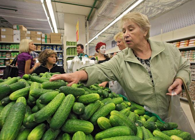 Женщина выбирает огурцы в супермаркете